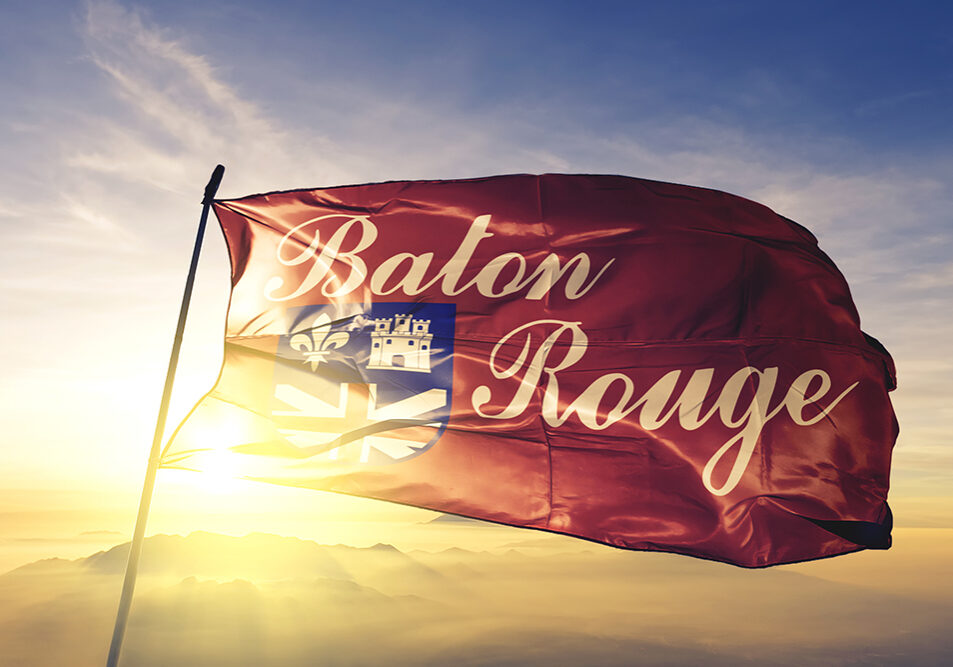 Baton Rouge city capital of Louisiana flag textile cloth fabric waving on the top sunrise mist fog