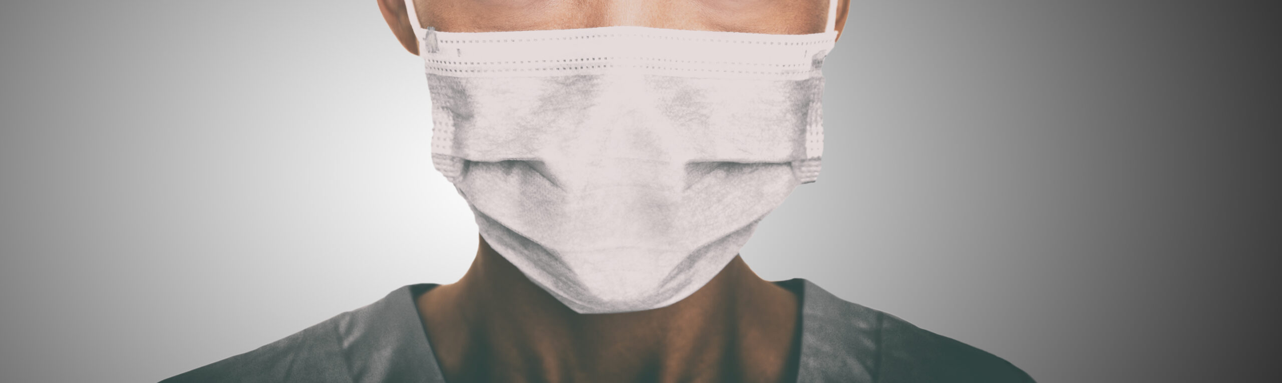 A healthcare worker wears a mask while facing the camera in front of a neutral background.