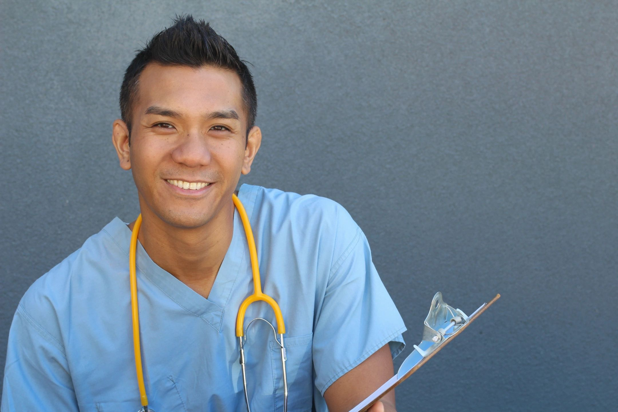 Man in blue scrubs with a clipboard