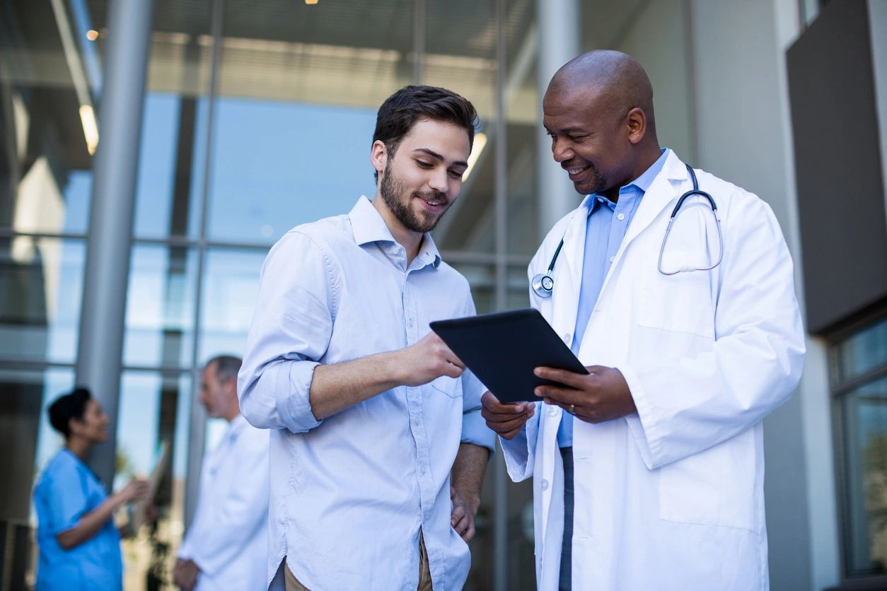 Doctor with a clipboard speaking to a man outside of a hospital