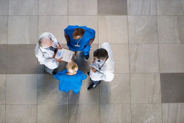 4 doctors talking in a circle while holding a chart