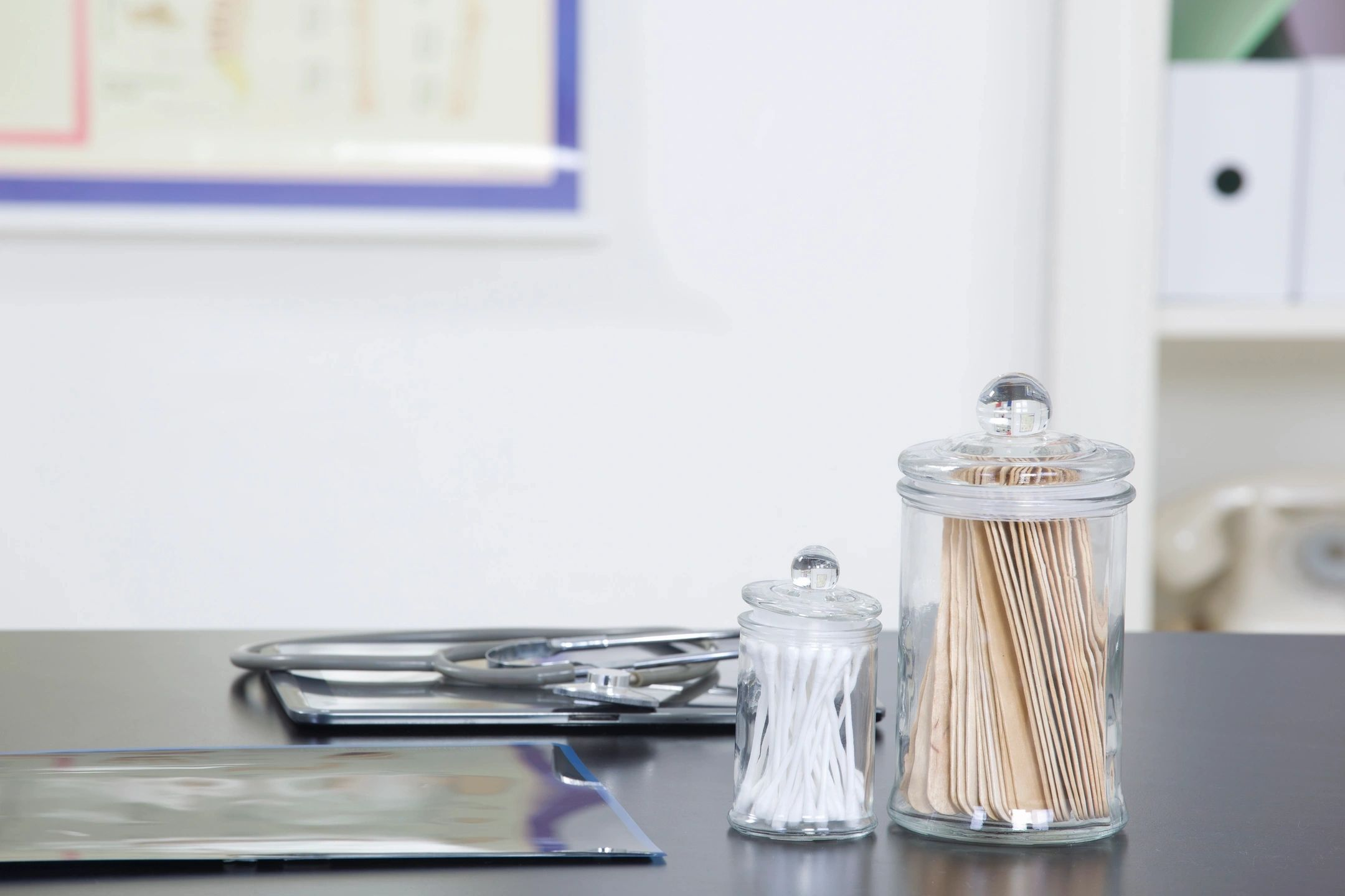 stethoscope, cotton swabs and tongue depressors sitting on a desk