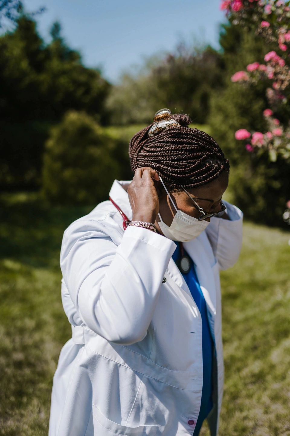 doctor in white coat putting on a facemask