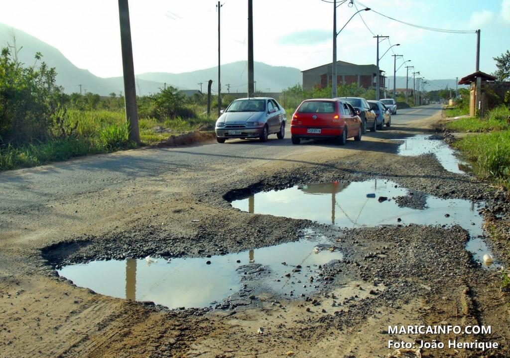 Carros desviam de enormes buracos na rua 66, no Jardim Atlântico. (Foto: João Henrique   Maricá Info)
