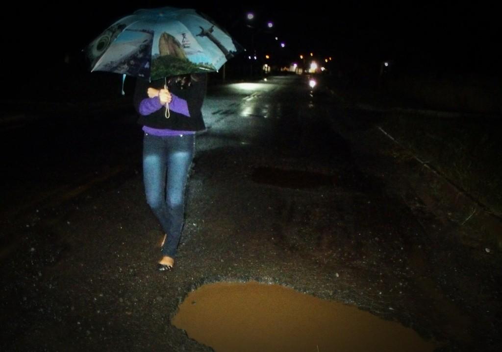 Pedestre caminha sob chuva fraca e desvia de buraco. (Foto: João Henrique   Maricá Info)