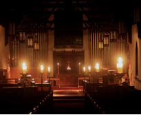 The St. John's Nave lit by candles for a worship service.