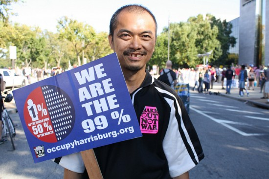 """Protester with """"We are the 99%"""" sign"""