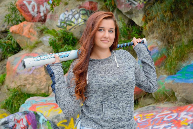 Senior girl posing with softball bat for senior portraits with a graffiti rock wall.
