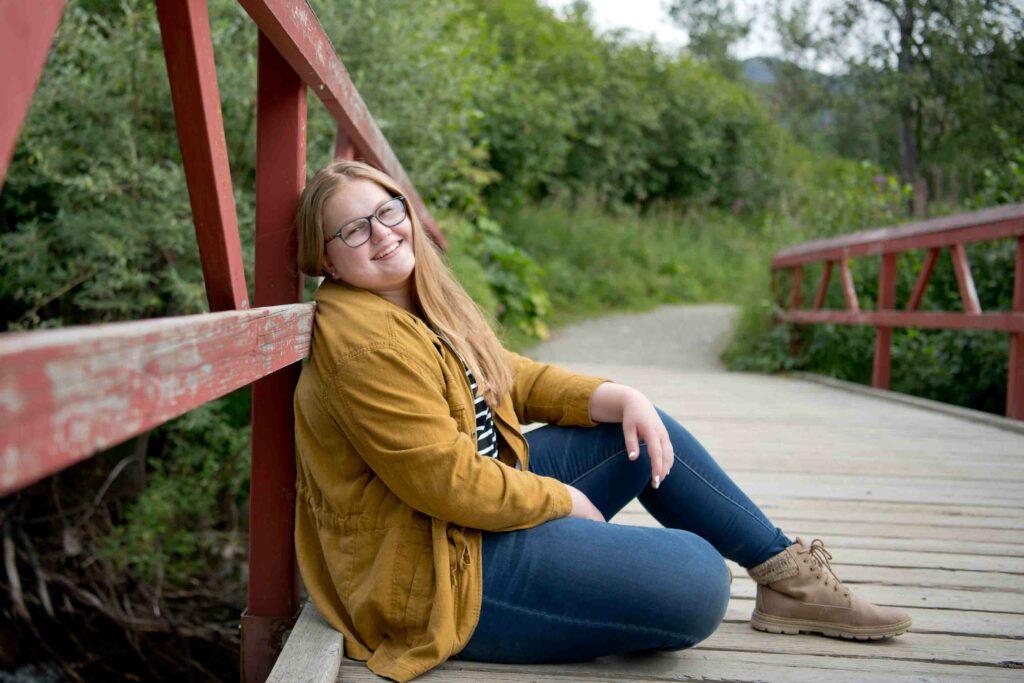 Plus size senior girl with glasses posing on hiking trail in Palmer, Alaska.