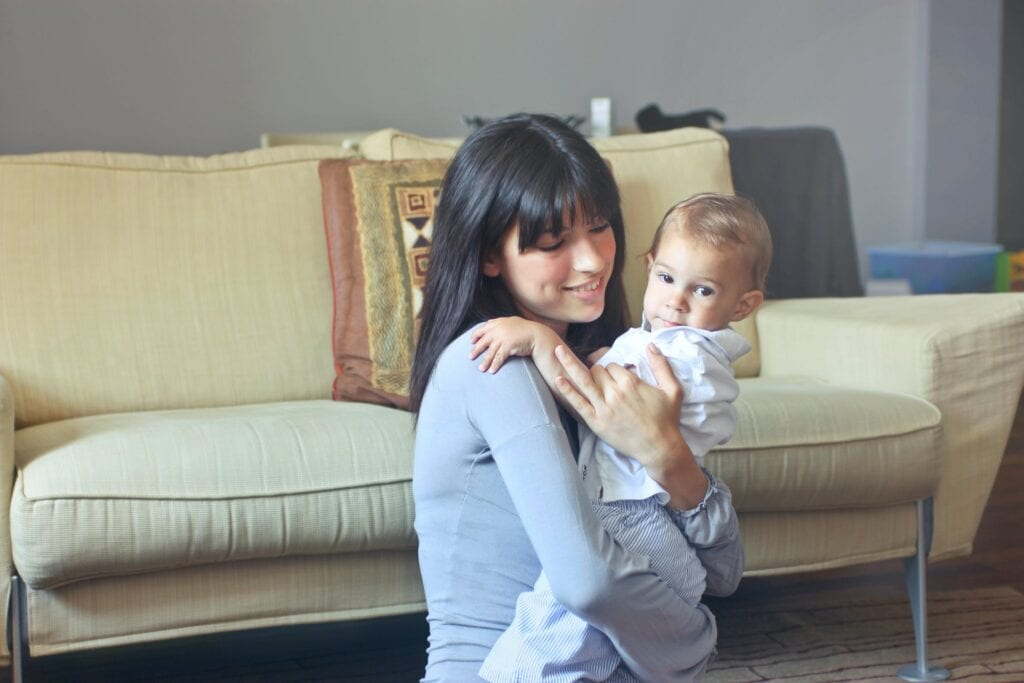 nanny or babysitter vs daycare woman holding baby