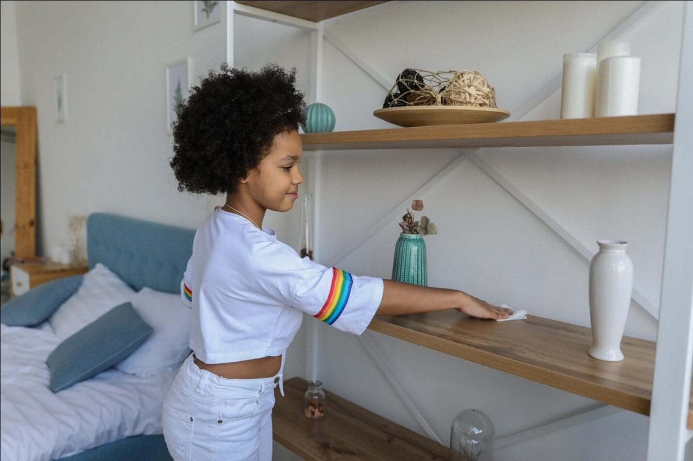 A young girl cleaning shelves.