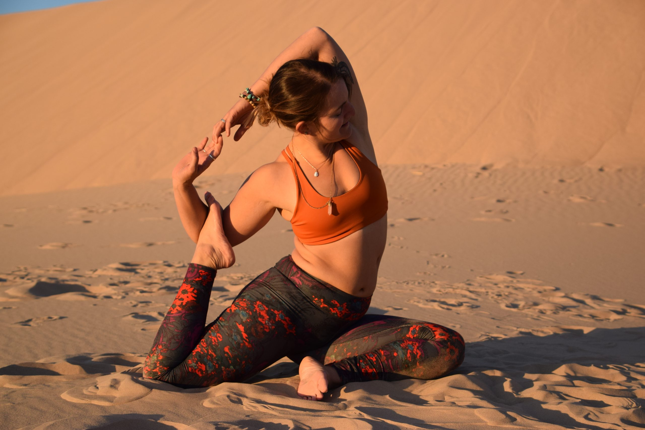 Têra Kaia ambassador and wildlife ecologist Betsy Dionne doing a yoga pose in her basewear top sports bra by a desert sand dune