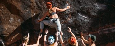 Woman climber bouldering in Moab Utah, supported by several female spotters all wearing Têra Kaia TOURA basewear top outdoor sports bras with strappy criss cross racerbacks