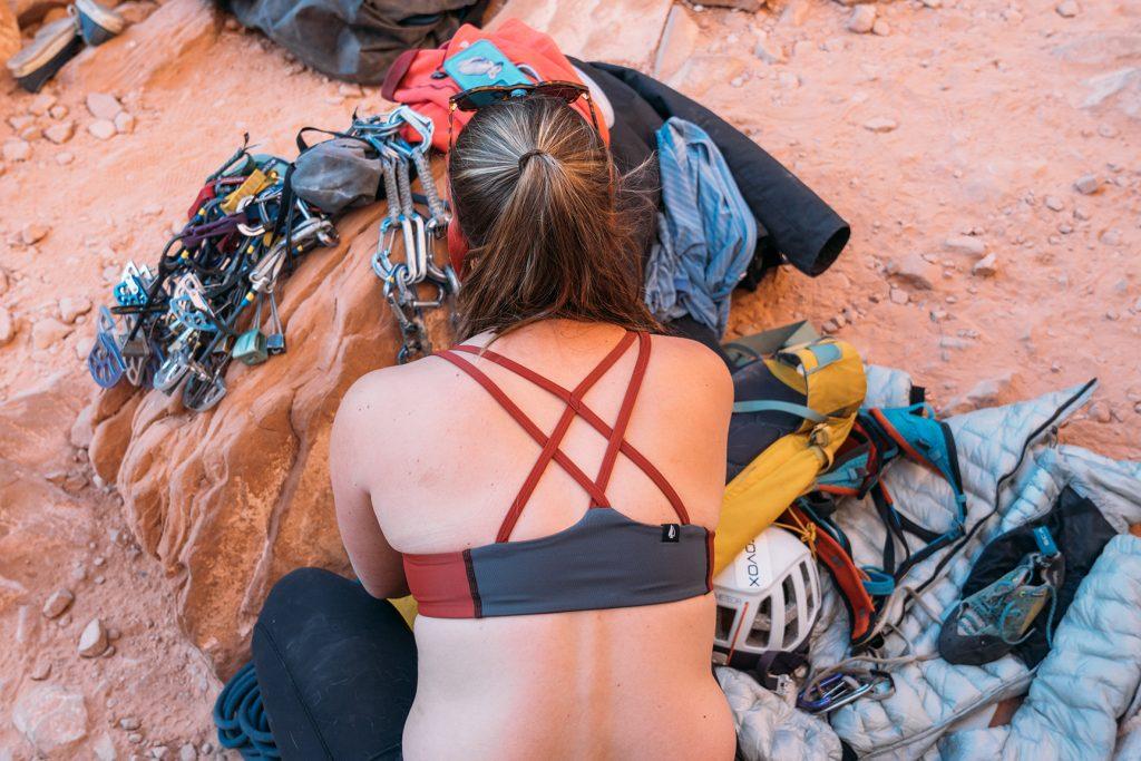 Woman racking up trad rock climbing gear Têra Kaia TOURA basewear top sports bras with strappy criss-cross racer back