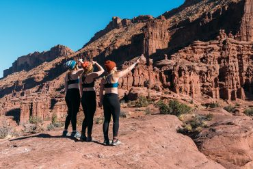 Women pointing at desert scenery in Moab wearing Têra Kaia TOURA basewear top sports bras with strappy criss-cross racer backs