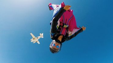 Têra Kaia ambassador and BASE jumper Jessica Maviano flying in the sky with a wing suit after jumping out of a plane