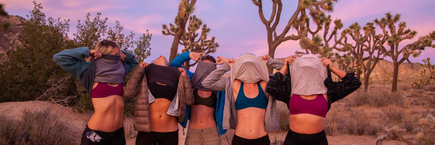 Women of the Têra Kaia collective in Joshua Tree National Park lifting shirts to expose TOURA basewear top outdoor sports bras with a pink and blue sunset