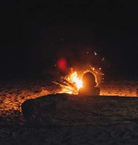 Woman sitting by campfire on beach