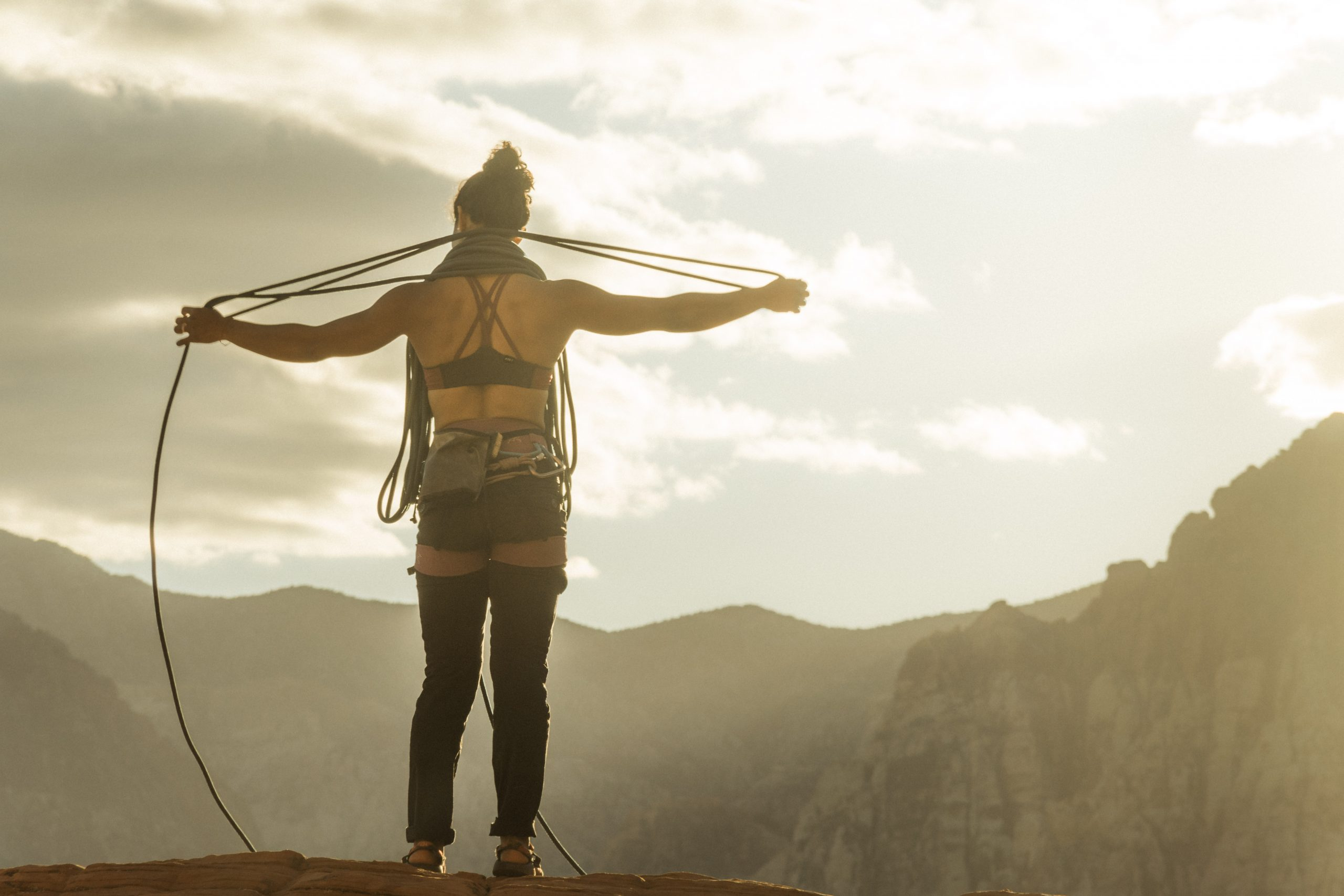 Female Rock Climber Maiza Lima in a Têra Kaia basewear top sports bra with a rope over a mountain view with sunlight.