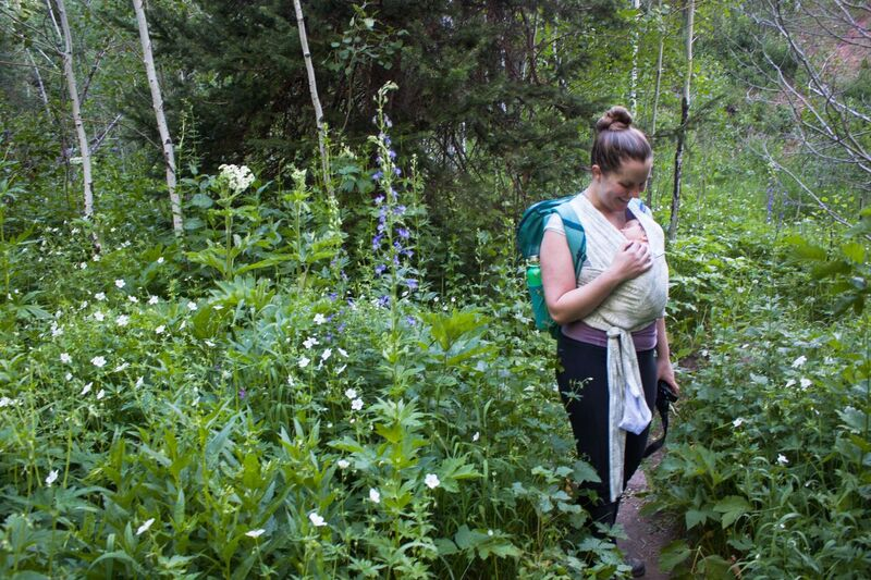 Têra Kaia ambassador and outdoor mother Rachel Taylor Jones hiking through a meadow with her child in a cloth baby wrap