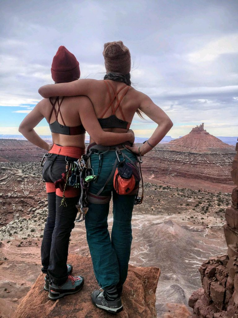 Têra Kaia ambassador Jessica Olson and friend hugging and looking at the view in Moab Utah after a day of rock climbing in their TOURA basewear top outdoor sports bras with strappy criss cross racer backs