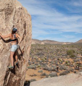 Joshua Tree Bouldering - Female rock climber bouldering in Joshua Tree National Park while wearing a Têra Kaia basewear sports bra