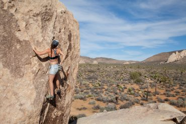 Joshua Tree Bouldering - Female rock climber bouldering in Joshua Tree National Park while wearing a Têra Kaia basewear sports bra
