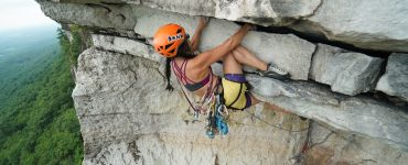 Têra Kaia ambassador and female rock climber Kathy Karlo leading a trad route in her TOURA basewear top outdoor sports bra