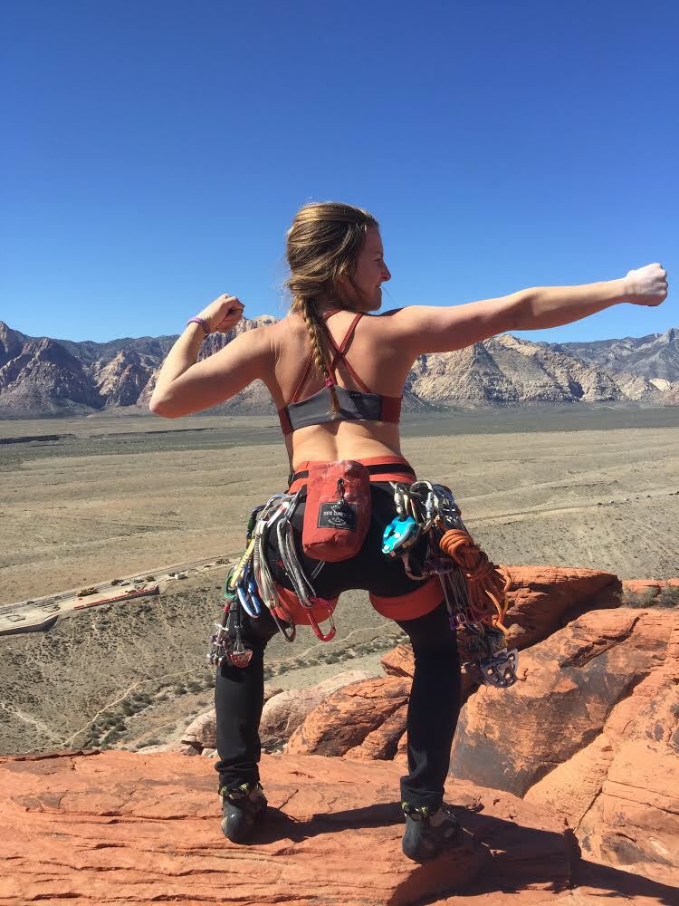Têra Kaia ambassador and female rock climber and guide posing in Moab with climbing gear in a TOURA basewear top outdoor sports bra with strappy criss-cross racerback