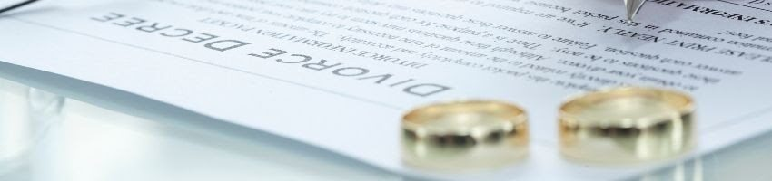 A pair of wedding rings over a divorce application symbolizing filing for divorce.