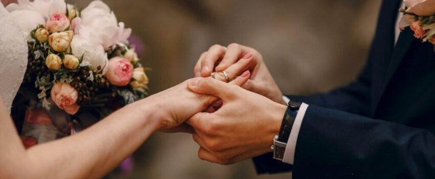 A bride and groom exchanging rings at a wedding.