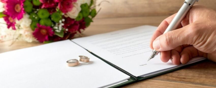 Women writing her name in a document to change her name after marriage