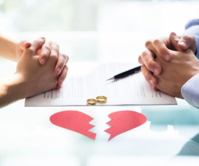 two couple facing and holding their individual hands with the broken hearted papers placed under the table
