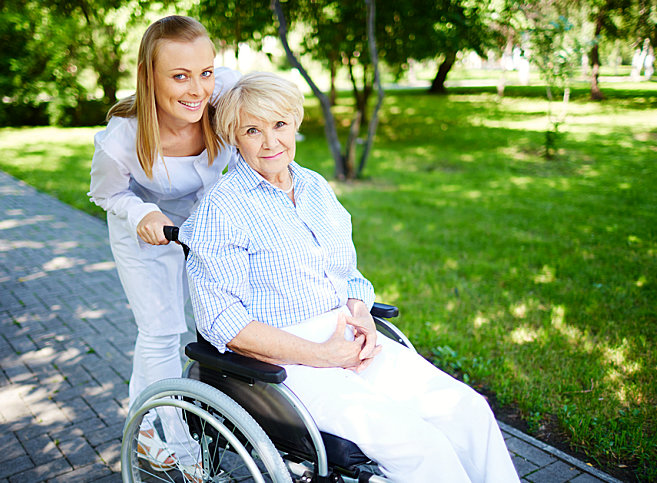 caregiver smiling with her senior patient on a wheelchair
