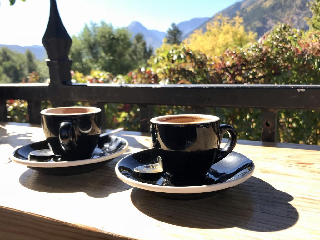 Two cups of espresso coffee on the terrace overlooking a mountain