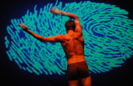dancer stands posed in front of digital finger print projected on screen