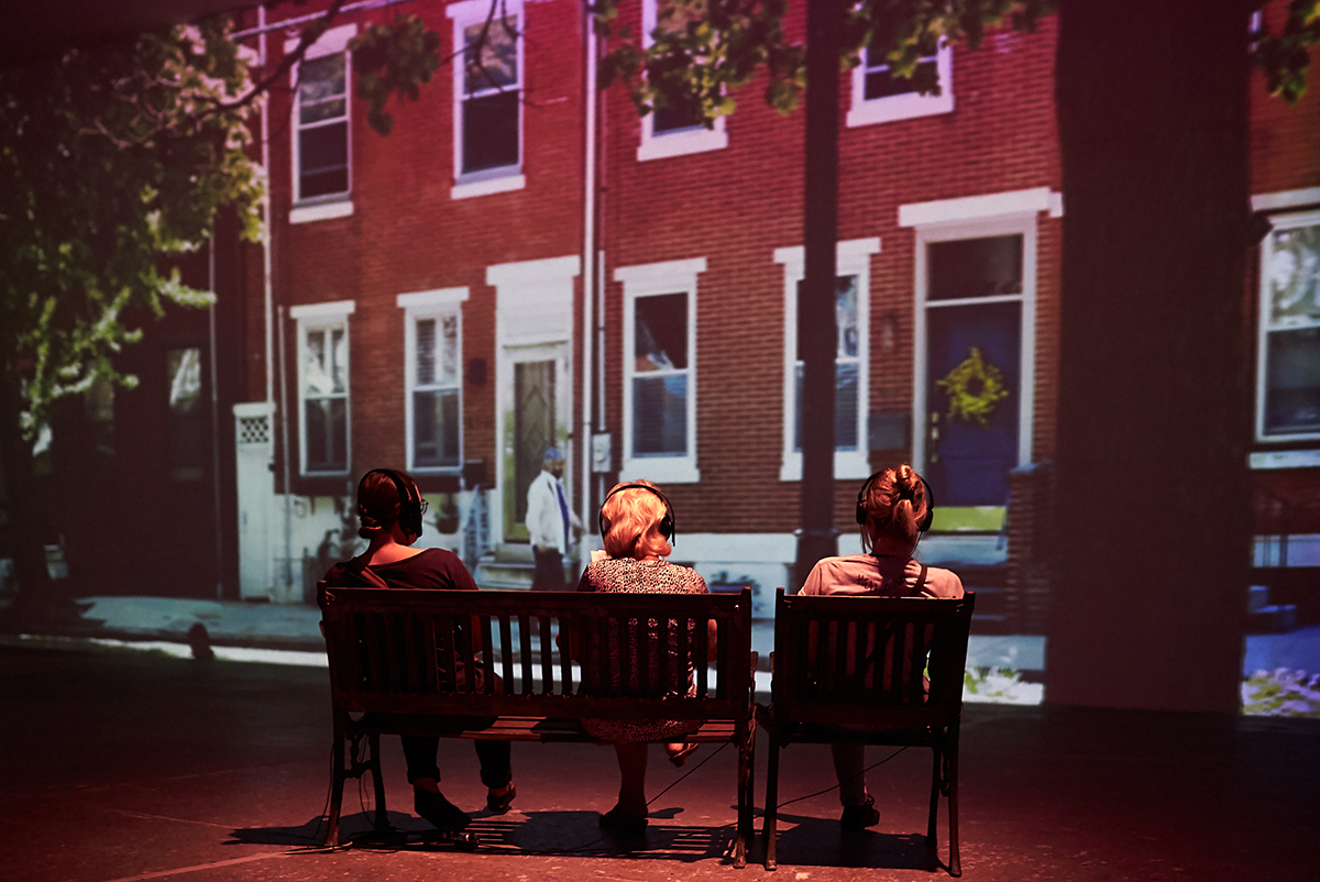 Three gallery visitors sitting on park bench in video installation