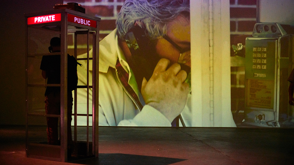 Person standing in 1960's telephone booth in a gallery with large projection of a man's face talking on phone on wall.
