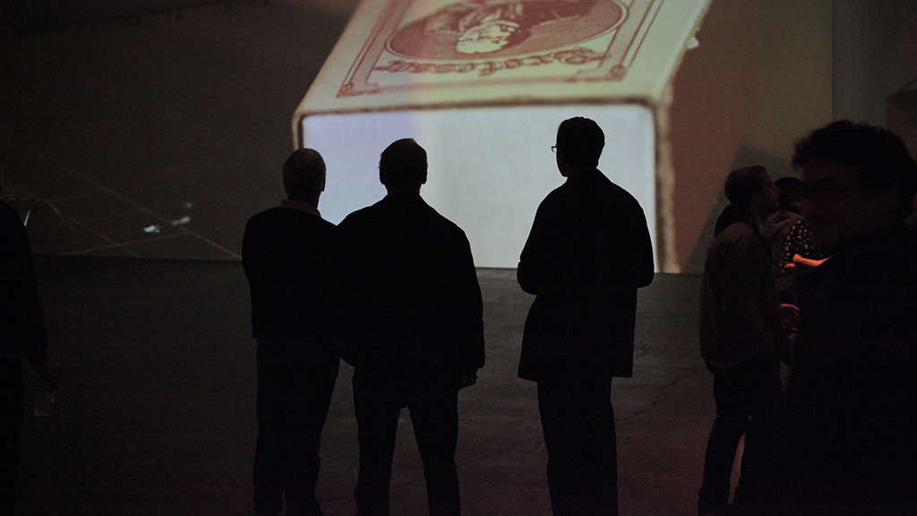 Silhouette of gallery visitors against large projection of matchbox