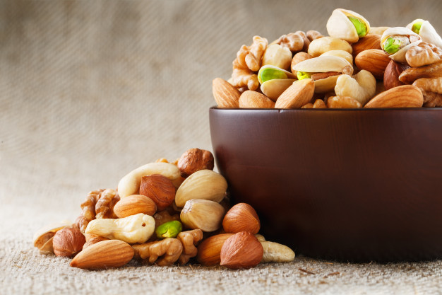 mix-different-nuts-wooden-cup-against-fabric-from-burlap-nuts-as-structure-background-macro-top-view_94046-1559