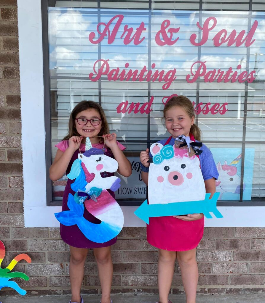 Two young girls hold their hand painted signs as they stand in front of the Art and Soul shop window. The signs are a unicorn with a mermaid tail and a bear with a flower crown.