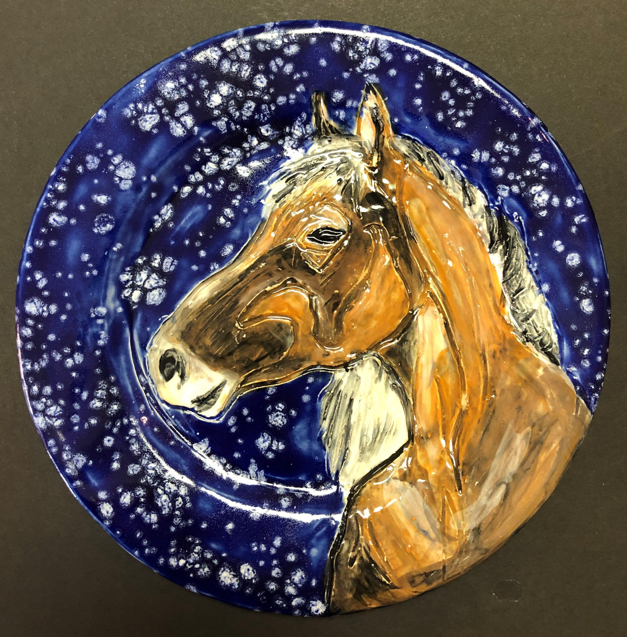 blue wall-mounted plate with a horse head on it