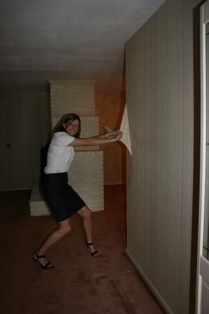 Kristen starts the renovation by stripping wallpaper in heels!