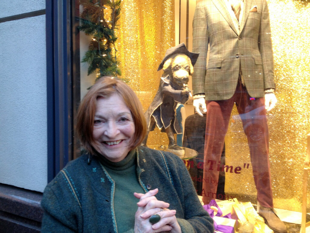 Elaine Badgley Arnoux posing with her art in the window of Wilkes Bashford