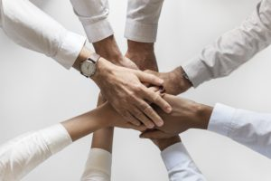 Team hands together for customer screening trust