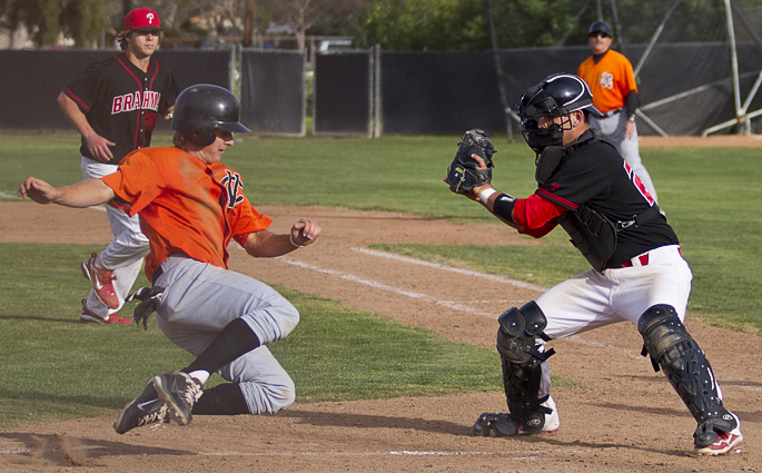 Ventura College Pirates second baseman Jared Patterson (5) slides into home as Los Angeles Pierce College Brahmas catcher Greg Koll (21) stands in front of home plate poised to tag the runner out. The Pirates came out victorious for this second match up between the two teams (4-6) Tuesday, February 21, 2012. Photo By: Angela Tafoya