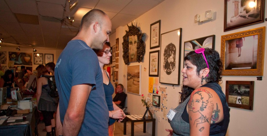 Event coordinator Erin Stone (right) describes the gallery setup to a visiting couple during the Canoga Park ARTrageous Art Walk in Canoga Park, Calif. on July 20, 2012. The community event was designed to bring the public and the artists together.