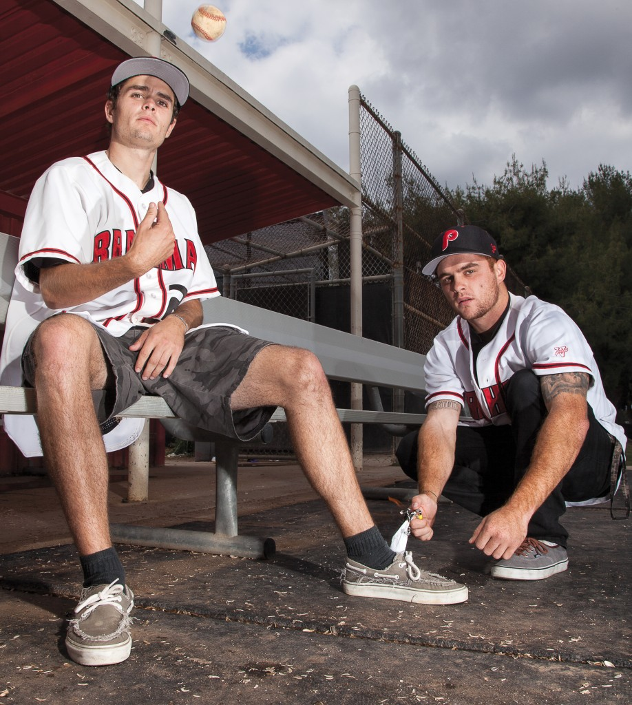 Jason Rowe tosses a baseball while Matt Rowe tries to light his foot on fire in this portrait recreating a typical prank done by baseball players on Monday, May 18 at the home dugout of Joe Kelly Field. Photo by: Mohammad Djauhari