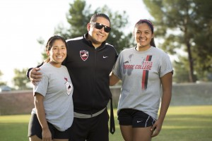 Alexis Lopez (left) and Alejandra Carvajal (right) pose with assistant coach Willie Diaz on the soccer field at Pierce College in Woodland Hills, Calif. on Oct. 24, 2016. Photo by Taylor Arthur