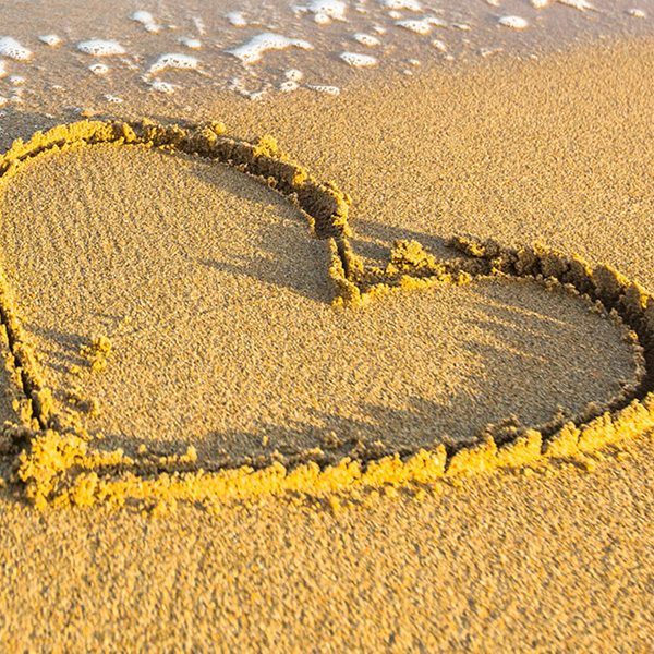 image of beach with heart drawn in sand